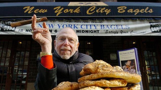 Un homme pose fièrement devant le commerce New York City Bagels