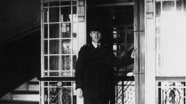 En 1930, un garçon d'ascenseur attend des passagers.