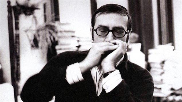 Gaston Miron jouant de l'harmonica.