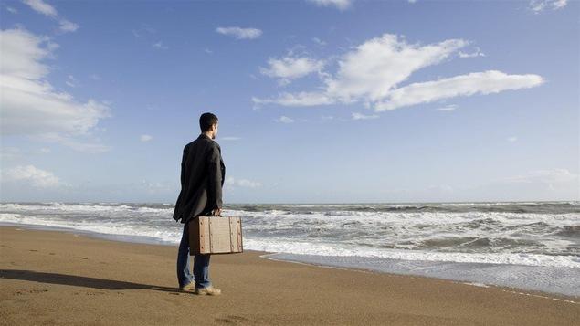 Un homme sur le bord de la mer avec une valise à la main