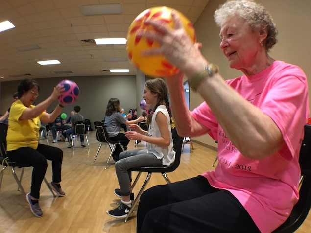 Une aînée participe à un jeu de ballon en compagnie de jeunes d'une école primaire.