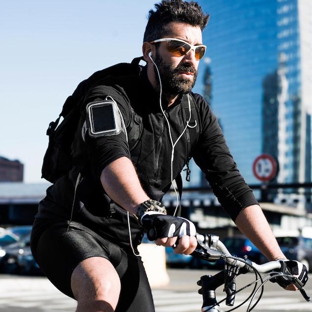 Un cycliste circule alors qu'il porte des écouteurs. Il porte aussi des verres fumés et semble se trouver en milieu urbain.