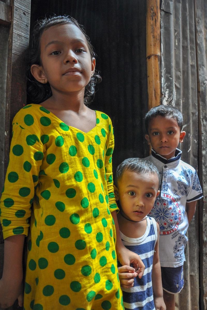 Trois enfants, une petite fille de sept ans et deux jeunes garçons, se tiennent devant la porte d'une habitation de tôle.