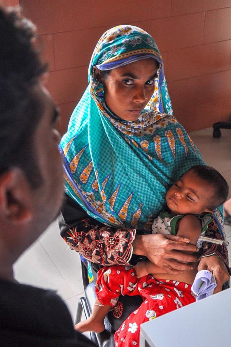 Un jeune enfant dort dans les bras de sa mère lors d'une consultation médicale.