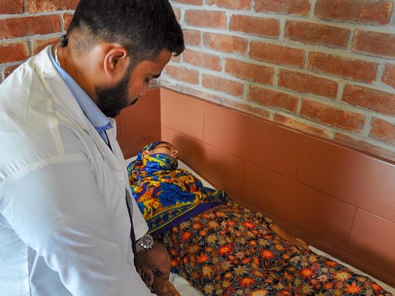 Dans un hôpital, un docteur examine une patiente couchée sur une civière.
