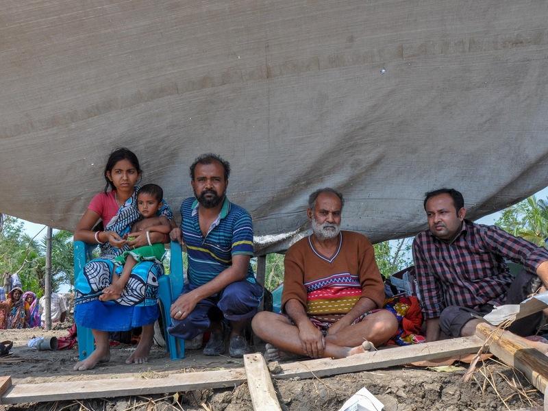 Trois hommes, une femme et un enfant sont assis sous une bâche, au milieu des débris.