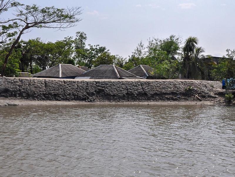 Une digue de boue et de sable bâtie aux abords d'une rivière. Derrière, des toits de tôle sont visibles.