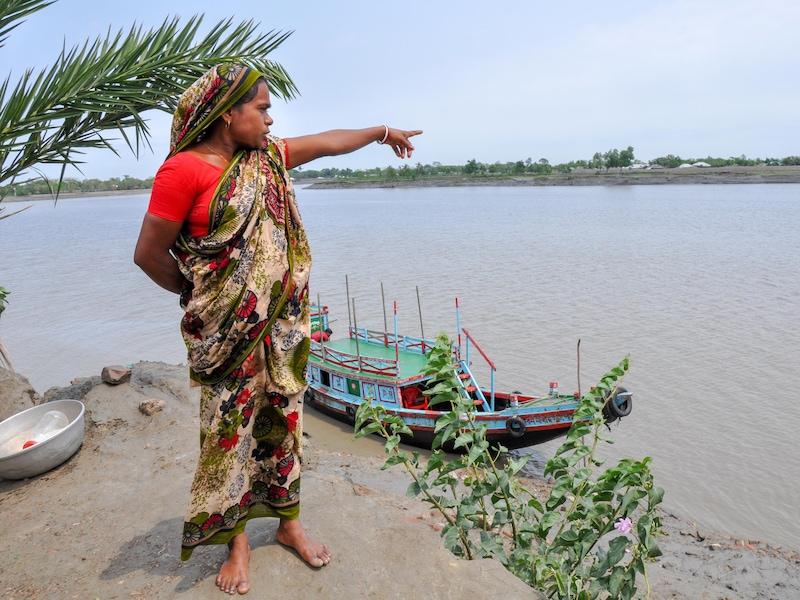 Une femme portant un sari pointe en direction de la rivière.