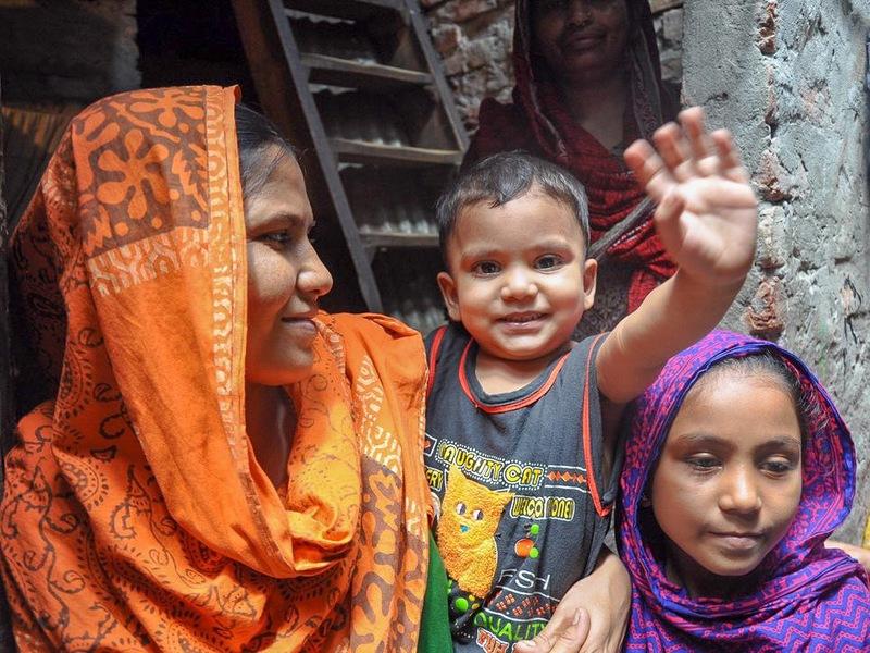 Une mère vêtue d'un voile et deux enfants : une fillette et un garçon, qu'elle tient dans ses bras.