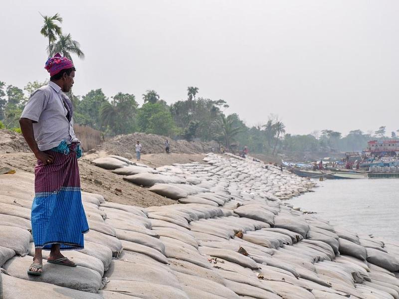Un homme observe les berges recouvertes de sacs de sable.
