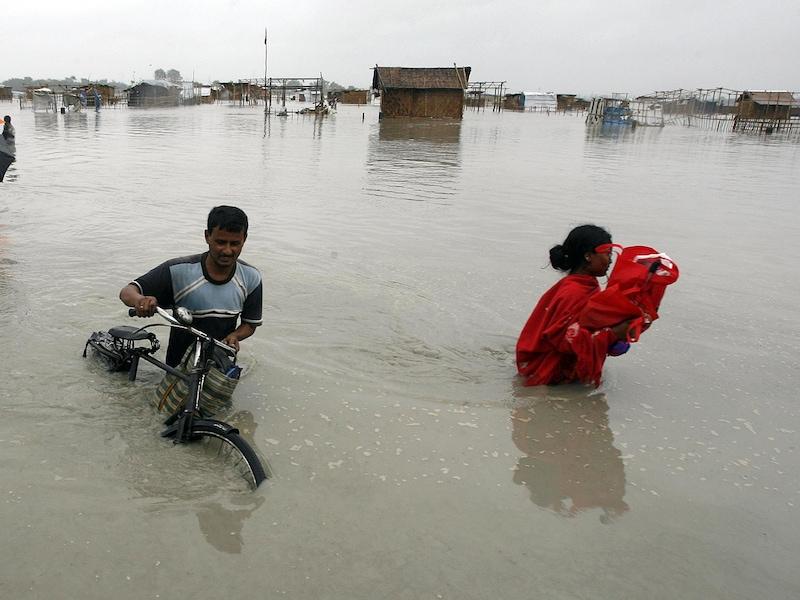 Une inondation détruit un village. Un homme pousse son vélo dans l'eau jusqu'à la taille. Une femme transporte ses biens.
