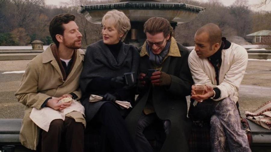 Trois hommes et une femme, en automne, assis sur le rebord d'une fontaine