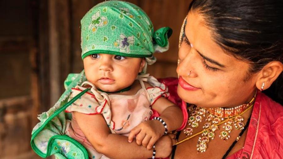 Un bébé  dans les bras de sa mère, dans un village du Rajasthan, en Inde