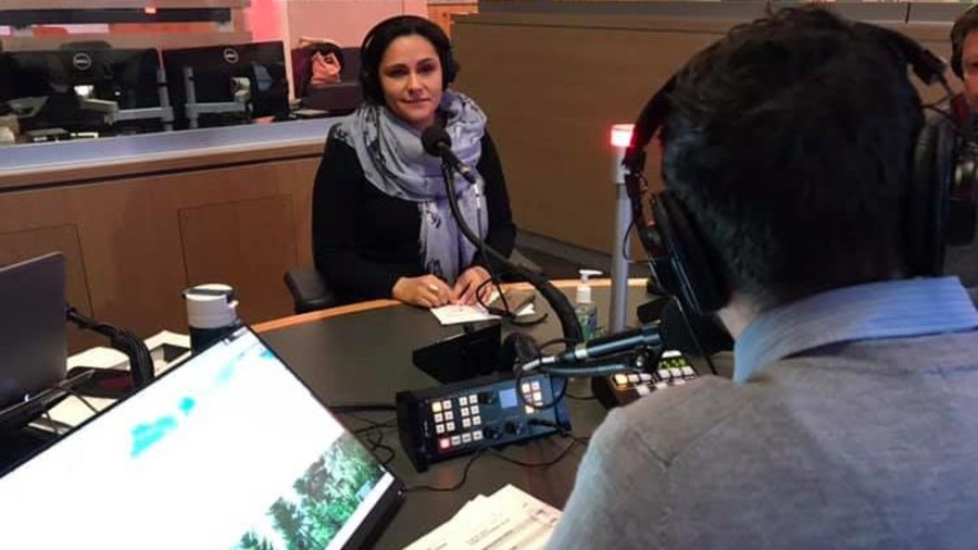 Erika Cantu parle au micro à la station de Radio-Canada Acadie.