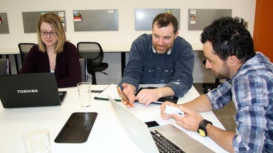 Trois personnes travaillent autour d'une table avec des ordinateurs portables.