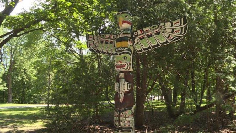 Le totem dressé dans le parc à côté des arbres