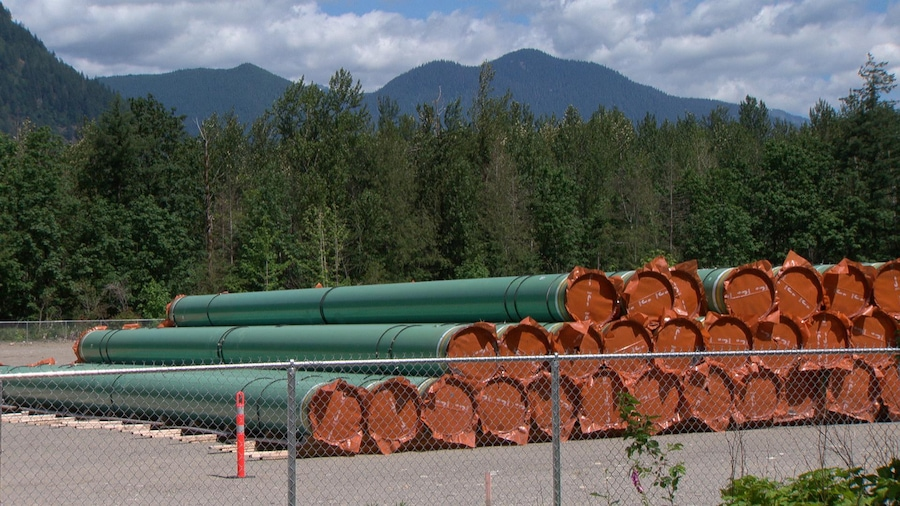 Des tuyaux entreposés dans une cour clôturée