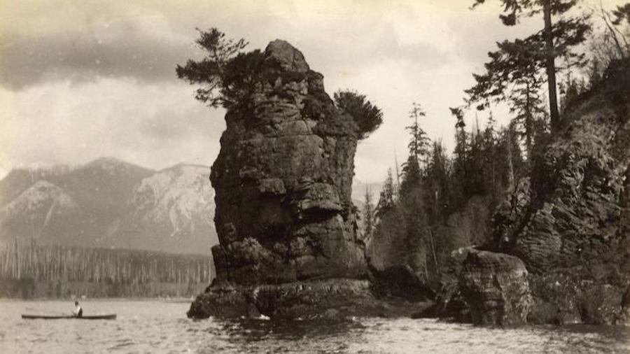 Une personne dans un canot se promène sur l'eau près d'un grand rocher avec montagnes en toile de fond