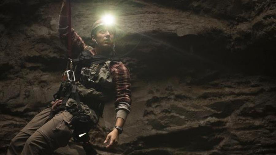 Samian, dans son rôle de jeune archéologue, est suspendu au moyen d'un harnais dans un énorme trou, s'éclairant à l'aide d'une lampe frontale.
