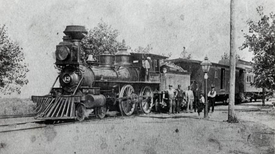 Photo du train à l'arrêt avec des personnes à côté de la locomotive.