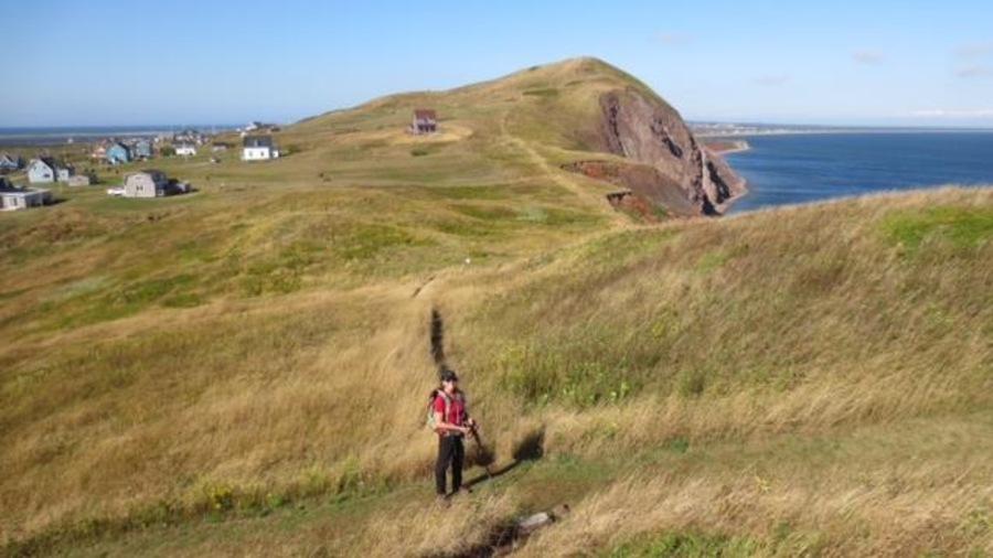 Des collines avec de la verdure et des maisons aux Îles-de-la-Madeleine.