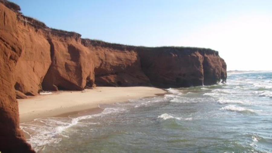 Une falaise rouge, une plage et la mer aux Îles-de-la-Madeleine