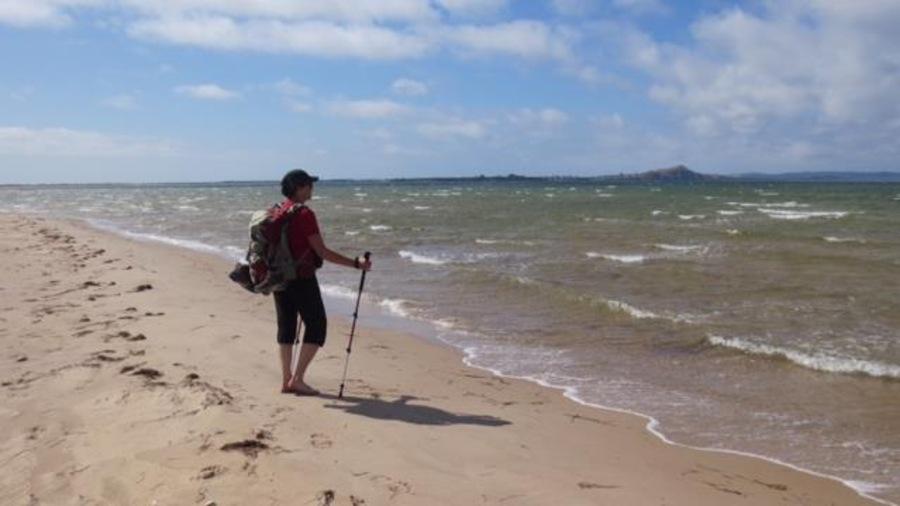 Joëlle Pineault pieds nus sur une plage des Îles-de-la-Madeleine