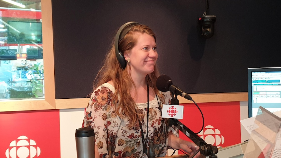 Une femme est photographiée devant un micro, dans un studio de radio.