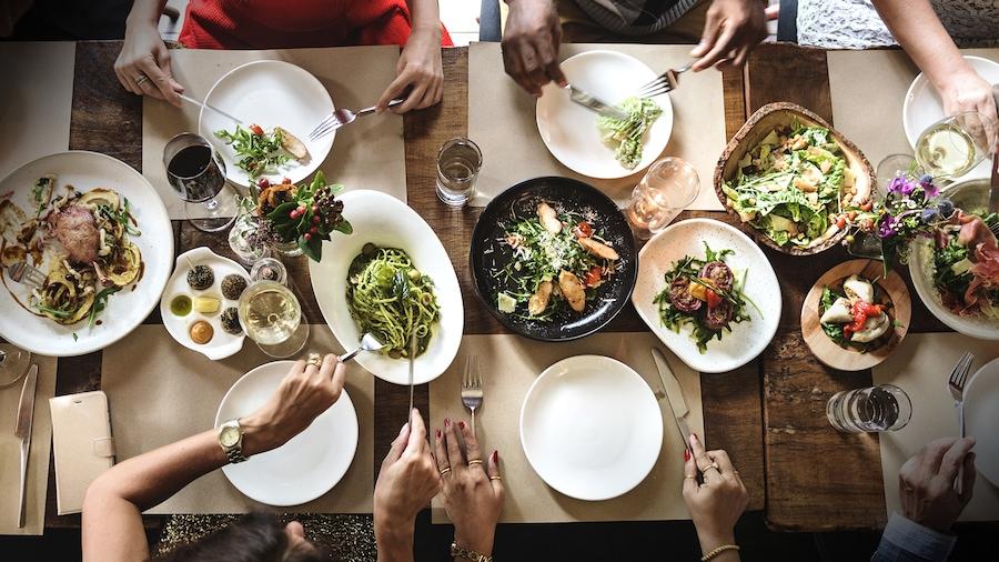 Il y a six personnes à table, ils mangent des champignons, des pâtes, de la salade et d'autres mets.