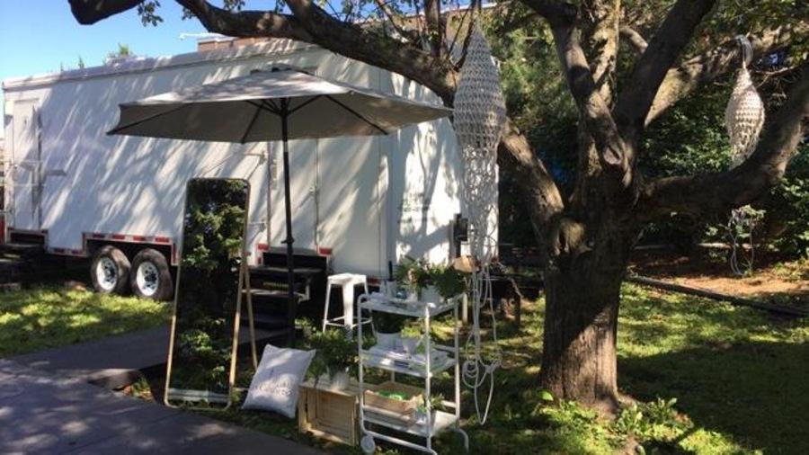 Sous un arbre, une roulotte blanche devant laquelle est disposé un parasol, un miroir et une petite étagère avec des produits.