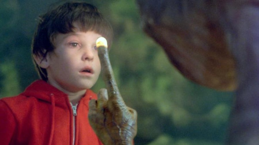 E.T. l'extra-terrestre lève le doigt en montrant le ciel devant Elliot (Henry Thomas).