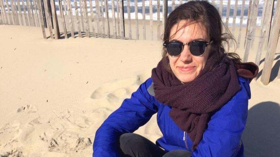 Elle est assise sur une plage, foulard au cou et manteau bleu.