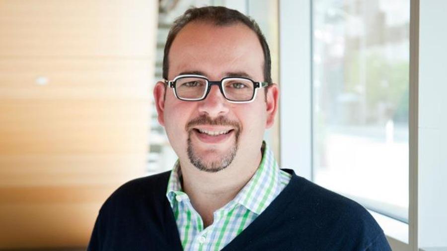 Portrait d'un homme portant des lunettes, une chemise carreautées et une veste marine.