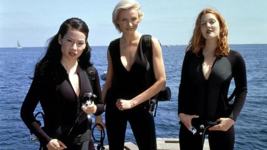 Trois jeunes femmes en tenues de plongée, sur un bateau.