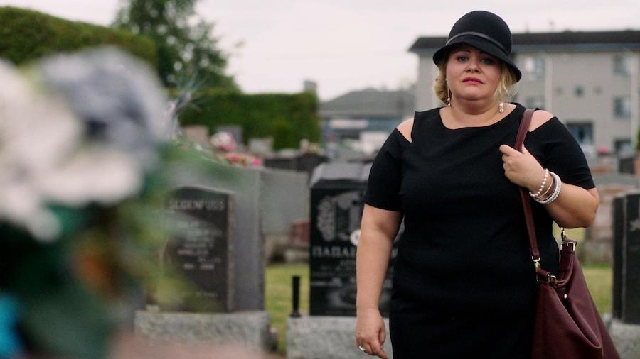 Une veuve dans un cimetière regarde une pierre tombale. Elle porte du noir et un chapeau.