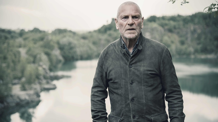 Un homme se tient debout devant un lac.