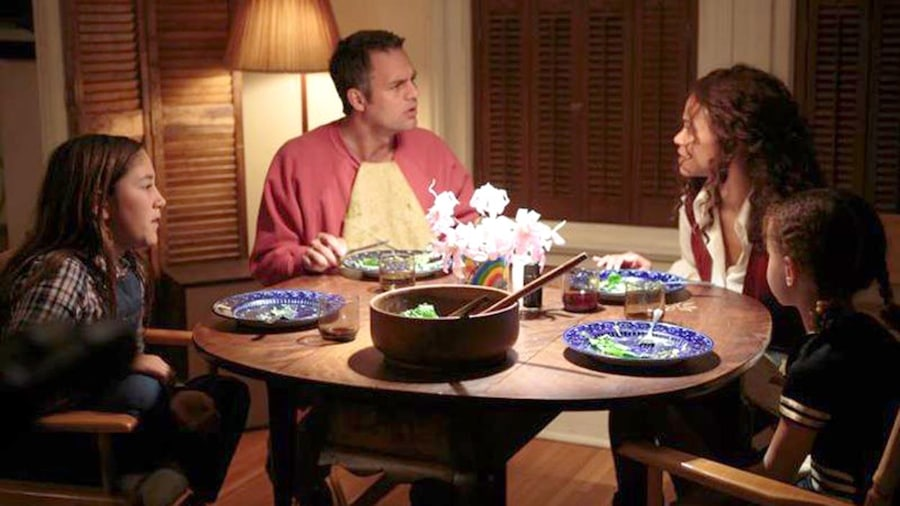 Un couple et deux fillettes autour d'une table ronde.