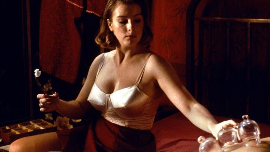 Une femme en jupe et sous-vêtements colle des ventouses sur le dos d'un homme.