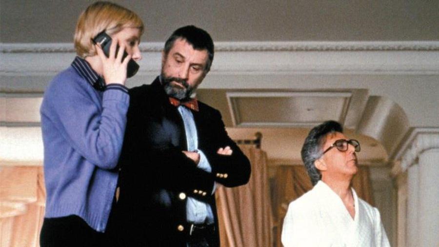 Une femme parle au téléphone à côté d'un homme debout et d'un autre assis.