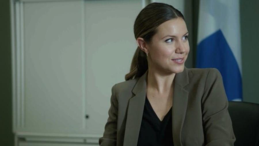 Nadine est assise dans le bureau de Daniel avec un petit sourire en coin.