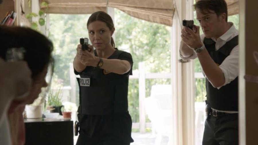 Les deux agents pointent leur arme vers le preneur d'otage.