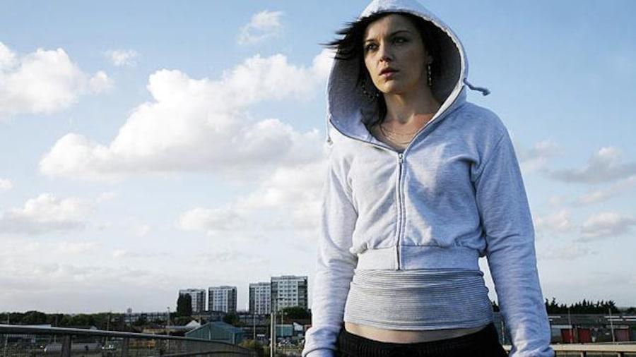 Une jeune fille avec une capuche sur la tête, sur un pont.