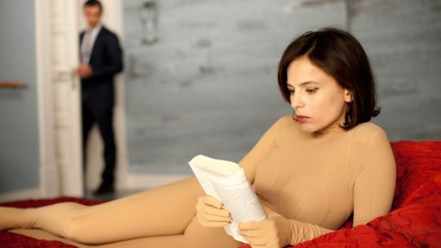 Une jeune femme allongée sur un lit rouge en combinaison couleur chair