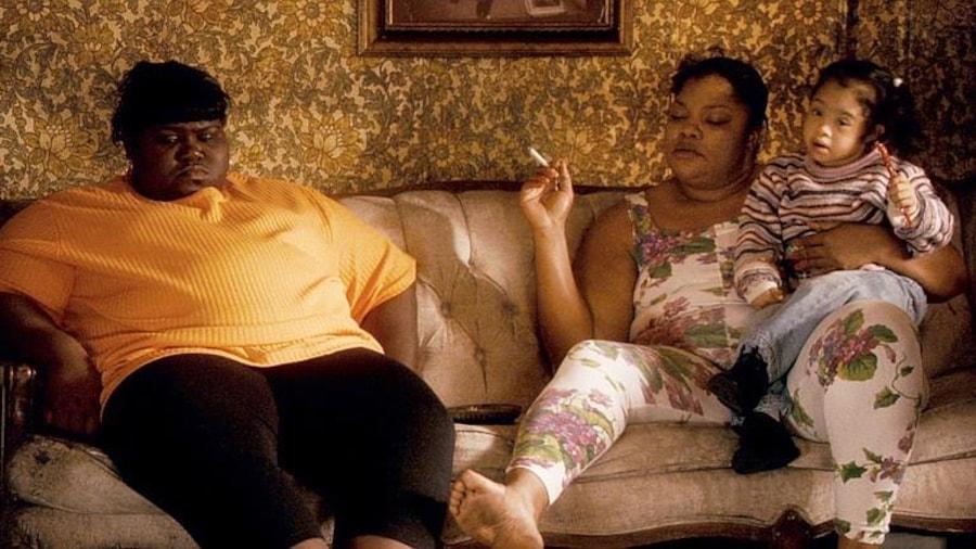 Une femme obèse assise sur un canapé à côté d'une femme portant un enfant sur les genoux.