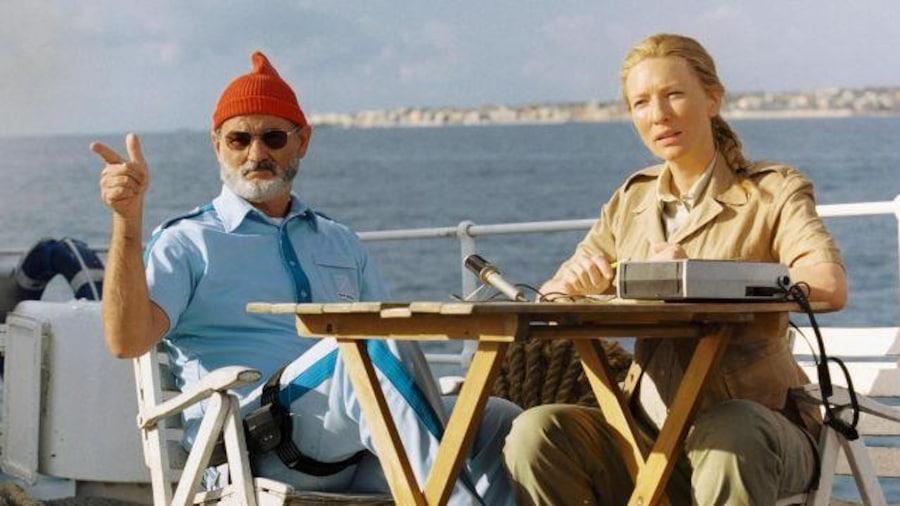 Sur un pont de bateau, une femme interviewe un homme en chemise bleue et bonnet rouge.