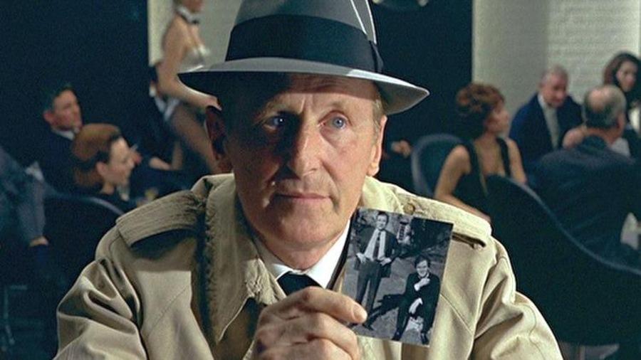 Un homme en imperméable et chapeau montre une photo en noir et blanc.