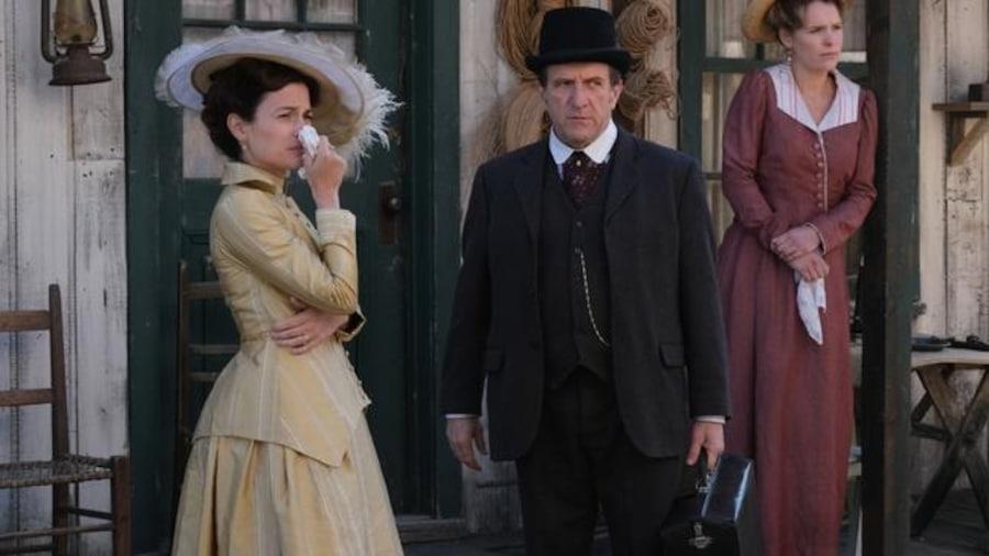 Les deux femmes et l'homme, habillés de vêtements d'époque, regardent au loin et semblent tristes.
