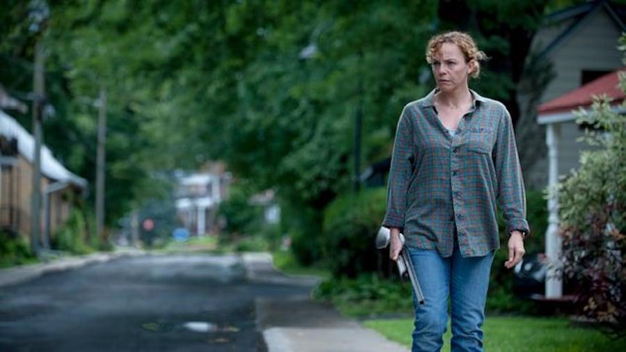 La comédienne marche dans la rue, carabine à la main, dans une rue de Fatale-Station.