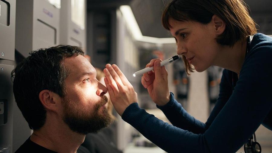 Une femme examine les yeux d'un homme avec un instrument lumineux.
