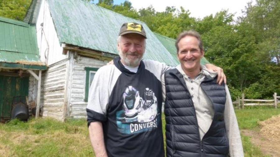 Deux hommes souriants s'enlacent devant une grange.